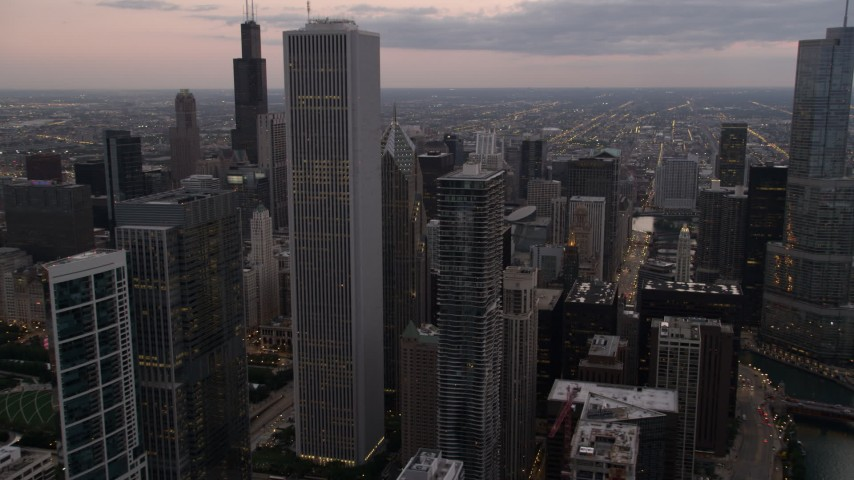 Chicago River and high-rises between Aon Center and Trump Tower at sunset, Downtown Chicago, Illinois Aerial Stock Footage | AX0003_080