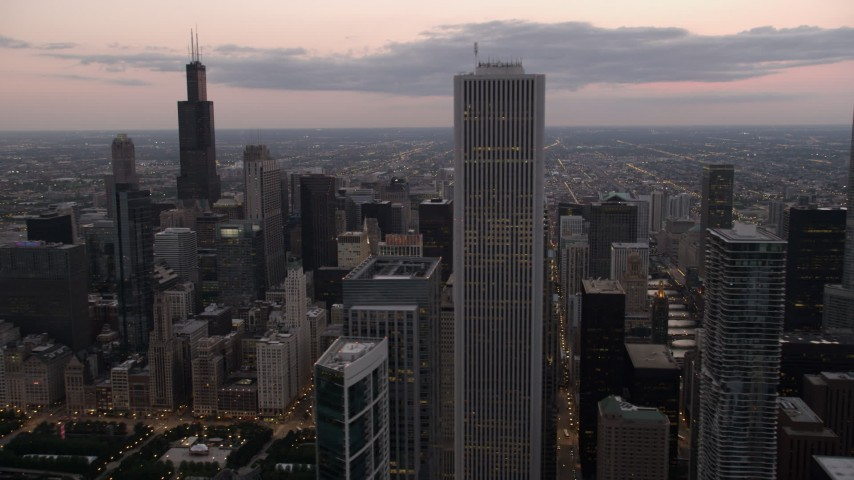 Flyby Aon Center with a view of Willis Tower, Downtown Chicago, Illinois, sunset Aerial Stock Footage | AX0003_081
