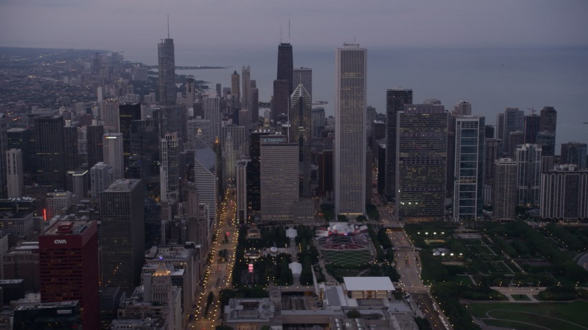 Tilt from Buckingham Fountain at Grant Park, revealing Downtown Chicago skyscrapers, on a hazy day at sunset, Illinois Aerial Stock Footage | AX0003_083