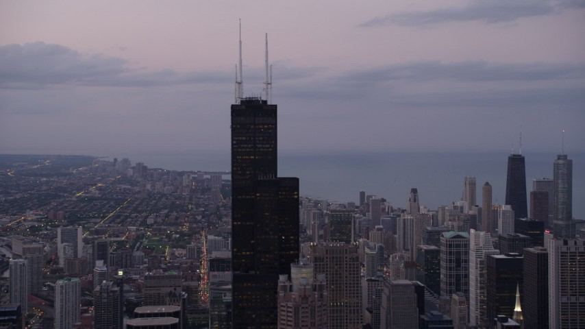 5K stock footage aerial video orbiting top of Willis Tower in Downtown Chicago, on a cloudy day at sunset, Illinois Aerial Stock Footage | AX0003_084