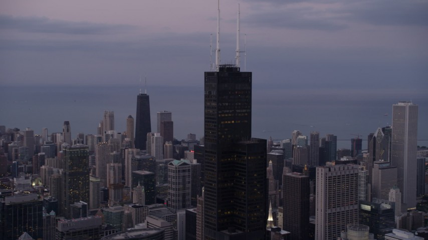 An orbit of the top of Willis Tower on a cloudy day at sunset, Chicago, Illinois Aerial Stock Footage | AX0003_085