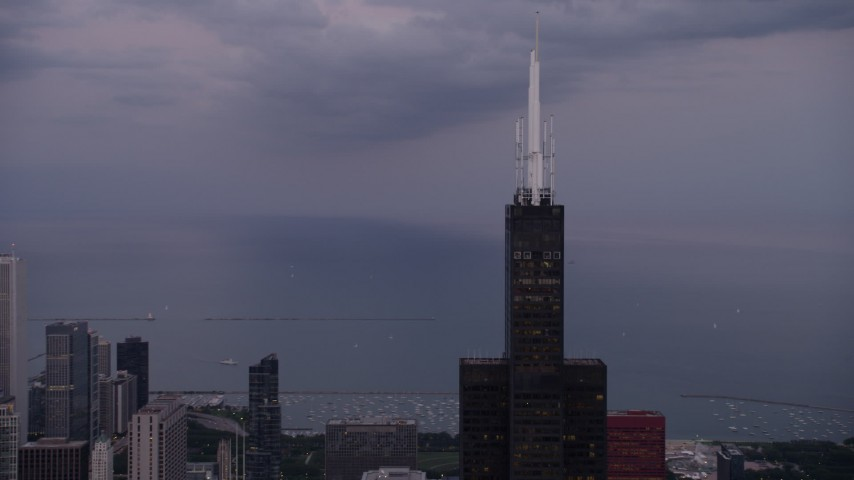 Orbiting around the top of Willis Tower, Downtown Chicago, Illinois, sunset Aerial Stock Footage | AX0003_086