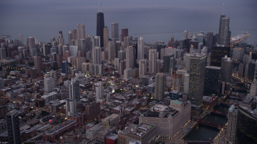 5K stock footage aerial video of flying by Downtown Chicago on a hazy sunset, Illinois Aerial Stock Footage | AX0003_087