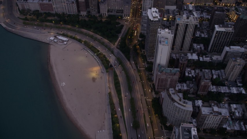 5K stock footage aerial video tilt from Lake Shore Drive and up N Michigan Avenue, reveal the Drake Hotel and Downtown Chicago buildings, at twilight, Illinois Aerial Stock Footage | AX0003_096