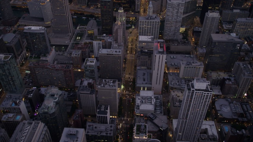 Bird's eye view of N Michigan Avenue through Downtown Chicago at twilight, Illinois Aerial Stock Footage | AX0003_098