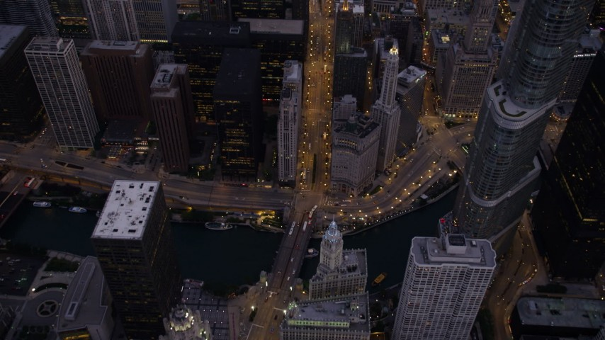 5K stock footage aerial video bird's eye of following N Michigan Avenue over the bridge spanning the the Chicago River, at twilight, Downtown Chicago, Illinois Aerial Stock Footage | AX0003_099