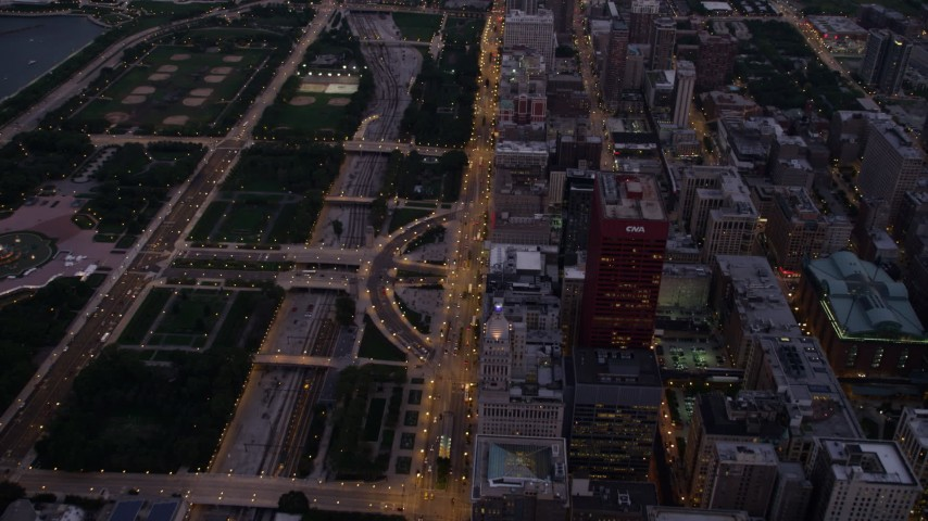 Bird's eye of N Michigan Avenue between Grant Park and Downtown Chicago buildings, Illinois, twilight Aerial Stock Footage | AX0003_101