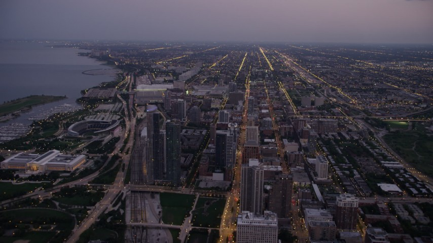 Bird's eye view of N Michigan Avenue by Grant Park, and tilt to South Chicago at twilight, Illinois Aerial Stock Footage | AX0003_102