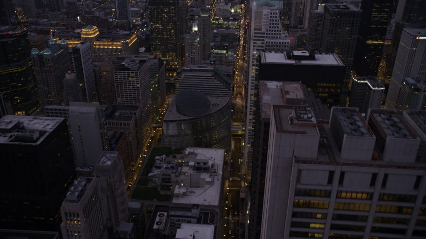 Follow N Clark Street to approach James R. Thompson Center, Downtown Chicago, Illinois, twilight Aerial Stock Footage | AX0003_106