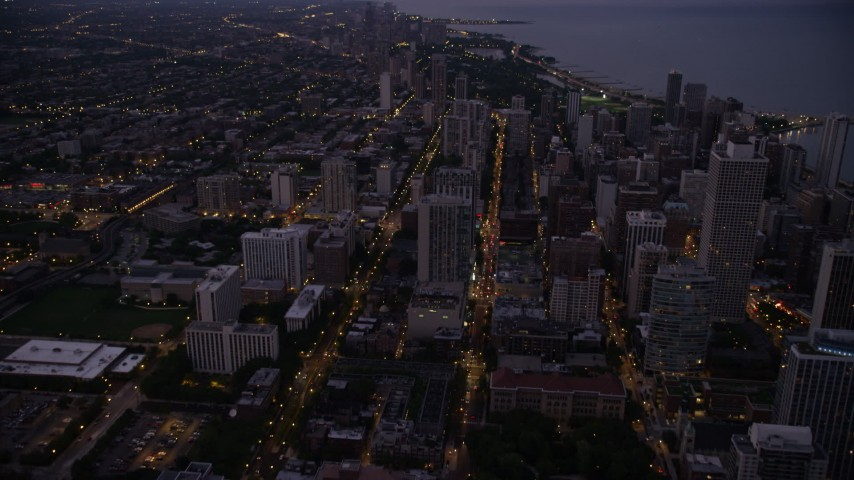 Tilt from N Clark Street and follow it north through Downtown Chicago, Illinois, twilight Aerial Stock Footage | AX0003_111