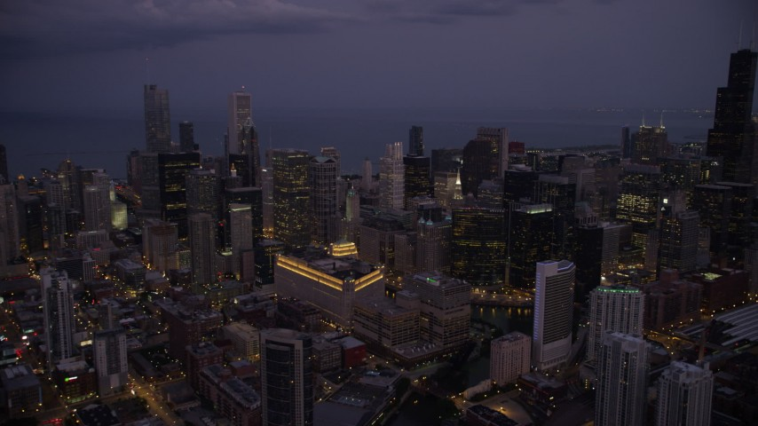 5K stock footage aerial video of a view across Downtown Chicago at sunset, with Lake Michigan in the background at twilight, Illinois Aerial Stock Footage AX0003_114 | Axiom Images