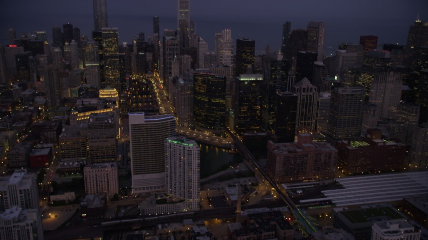 Tilt from train station to Chicago River and skyscrapers, Downtown Chicago, Illinois, twilight Aerial Stock Footage AX0003_115