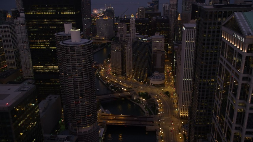 Fly over bridges and follow the Chicago River through downtown at twilight, Downtown Chicago, Illinois Aerial Stock Footage | AX0003_118