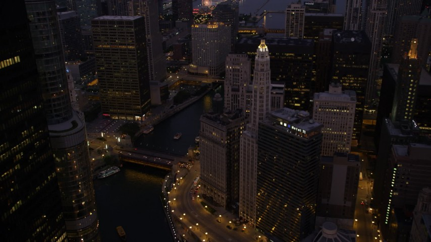 Following the Chicago River over bridges in Downtown Chicago, Illinois, twilight Aerial Stock Footage | AX0003_119
