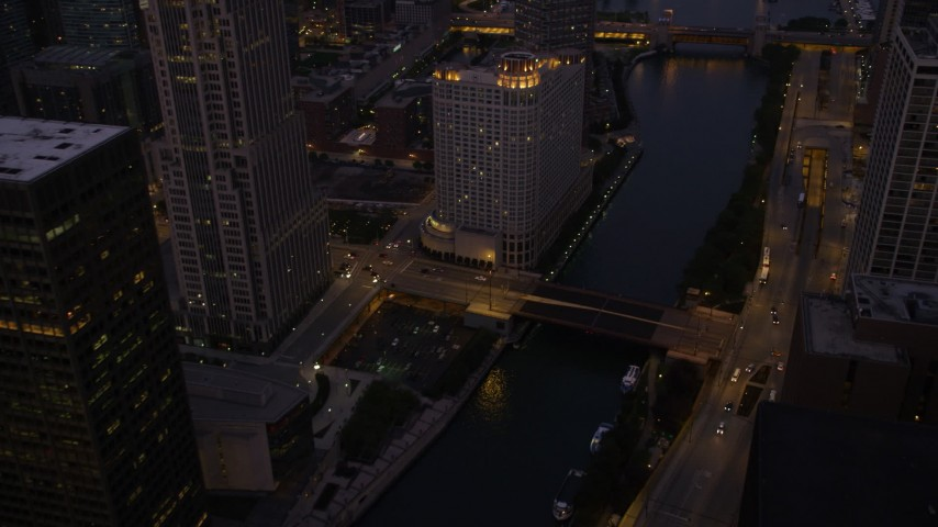 5K stock footage aerial video of flying over a bridge spanning the Chicago River in downtown at twilight, Downtown Chicago, Illinois Aerial Stock Footage | AX0003_120