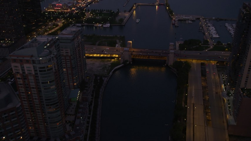 Following Chicago River over a bridge at the mouth of the river, revealing Navy Pier, Downtown Illinois, twilight Aerial Stock Footage | AX0003_121