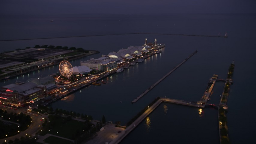 Flying by a Ferris wheel and rides on Navy Pier at twilight, Chicago, Illinois Aerial Stock Footage | AX0003_122