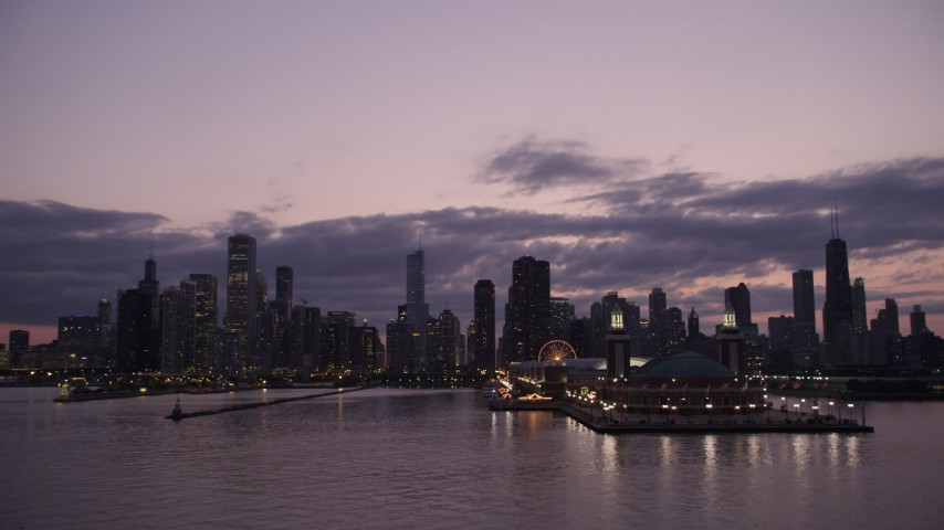 Passing by the end of Navy Pier with a view of the Downtown Chicago skyline at twilight, Illinois Aerial Stock Footage AX0003_125