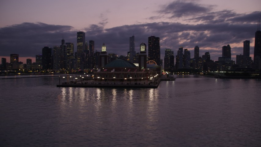 5K stock footage aerial video orbit around the end of Navy Pier, revealing Downtown Chicago skyline at twilight, llinois Aerial Stock Footage | AX0003_127