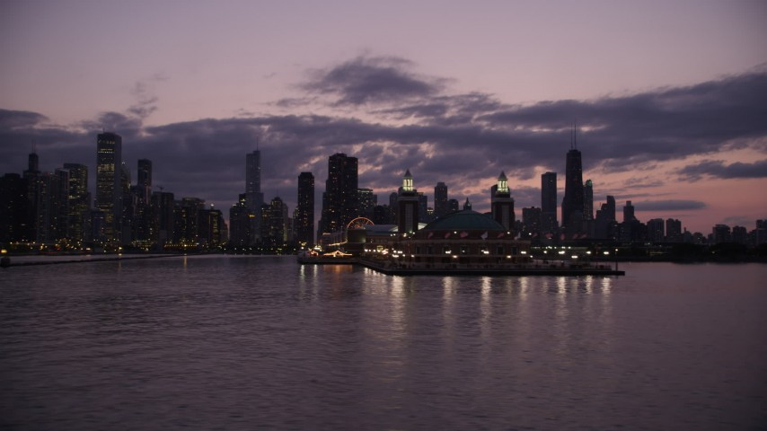 5K stock footage aerial video of flying by Navy Pier with the Downtown Chicago skyline in the background at twilight, Illinois Aerial Stock Footage | AX0003_128