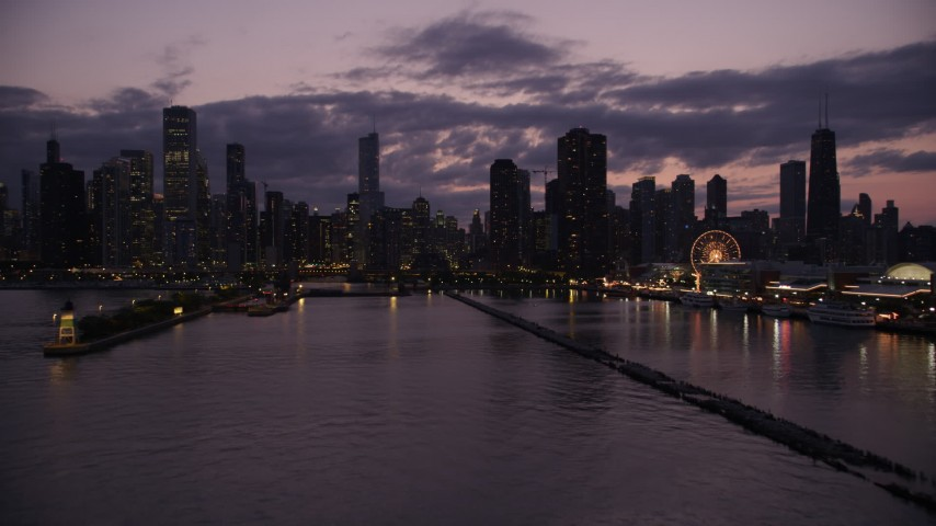 Flying over Lake Michigan to approach Downtown Chicago skyline at twilight, Illinois Aerial Stock Footage | AX0003_129