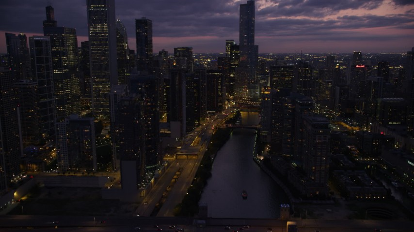 Tilt to reveal and approach the bridge at the mouth of the Chicago River in Downtown Chicago, Illinois, twilight Aerial Stock Footage | AX0003_131