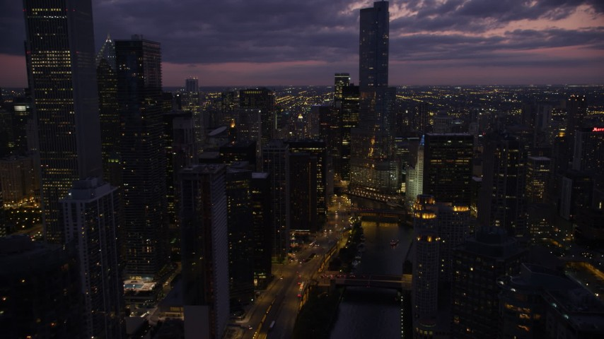 5K stock footage aerial video follow Chicago River through downtown toward Trump Tower Chicago at twilight, Illinois Aerial Stock Footage | AX0003_132