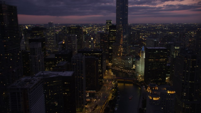 Following the Chicago River toward the base of Trump Tower Chicago at twilight, Illinois Aerial Stock Footage | AX0003_133