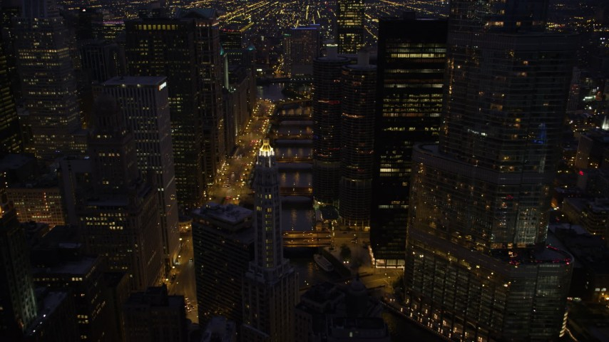 5K stock footage aerial video fly over Mather Tower and follow the Chicago River through downtown at night, Downtown Chicago, Illinois Aerial Stock Footage | AX0003_134