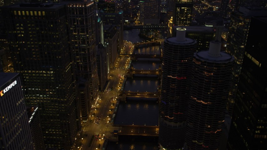 5K stock footage aerial video follow the Chicago River over bridges and tilt up, Downtown Chicago, Illinois, twilight Aerial Stock Footage | AX0003_135
