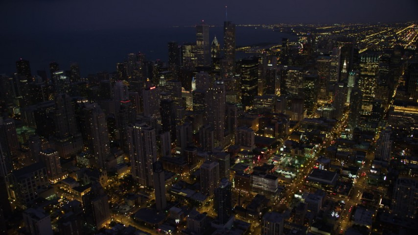 5K stock footage aerial video tilt up and approach Downtown Chicago skyscrapers and high-rises at night, Illinois Aerial Stock Footage | AX0003_141