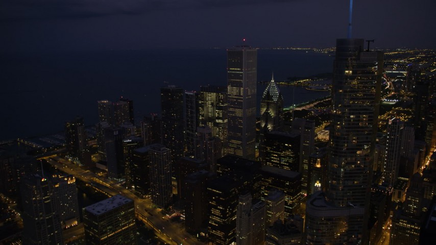 Passing Trump Tower Chicago to approach Aon Center and Two Prudential Plaza in Downtown Chicago, at night, Illinois Aerial Stock Footage | AX0003_144