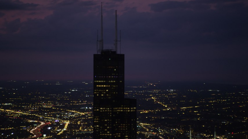 Orbiting the top of the Willis Tower skyscraper at night with clouds, Downtown Chicago, Illinois Aerial Stock Footage | AX0003_150