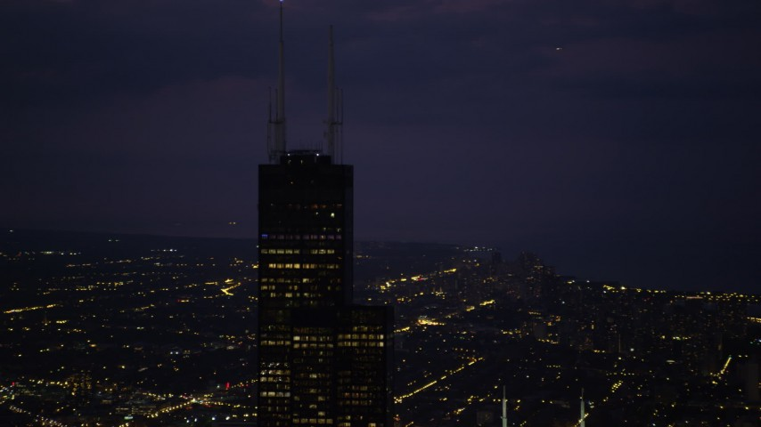 Orbiting the top of Willis Tower, Downtown Chicago, Illinois, night Aerial Stock Footage | AX0003_151