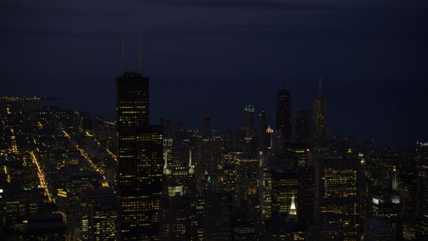 Flying by Willis Tower and Downtown Chicago cityscape, Illinois, night Aerial Stock Footage | AX0003_152