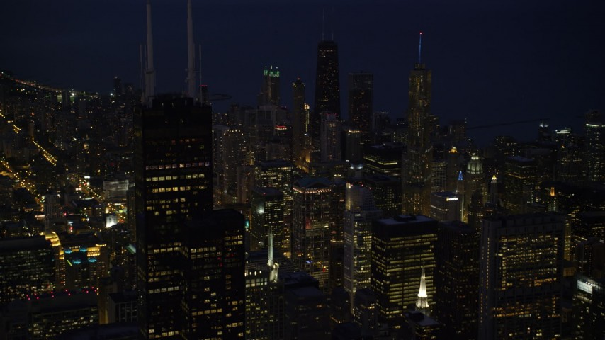 5K stock footage aerial video approach Willis Tower and Downtown Chicago skyscrapers at night, and tilt down, Illinois Aerial Stock Footage | AX0003_154