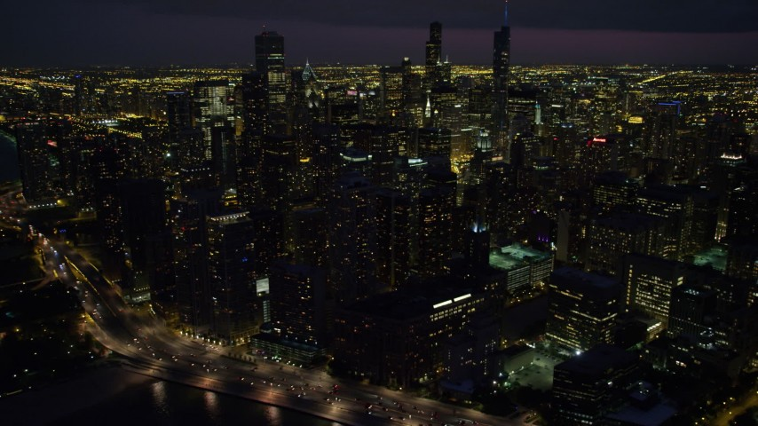 5K stock footage aerial video of flying by Downtown Chicago cityscape, at night with clouds, Illinois Aerial Stock Footage | AX0003_161