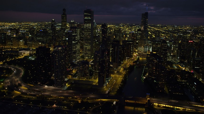 5K stock footage aerial video of flying by Chicago River and downtown skyscrapers on a cloudy night, Downtown Chicago, Illinois Aerial Stock Footage | AX0003_164