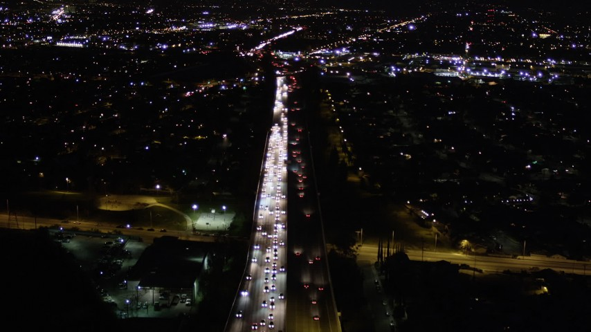 Fly Over Heavy Nighttime Traffic on Interstate 170 through Sun Valley and Tilt Up Aerial Stock Footage | AX0004_002