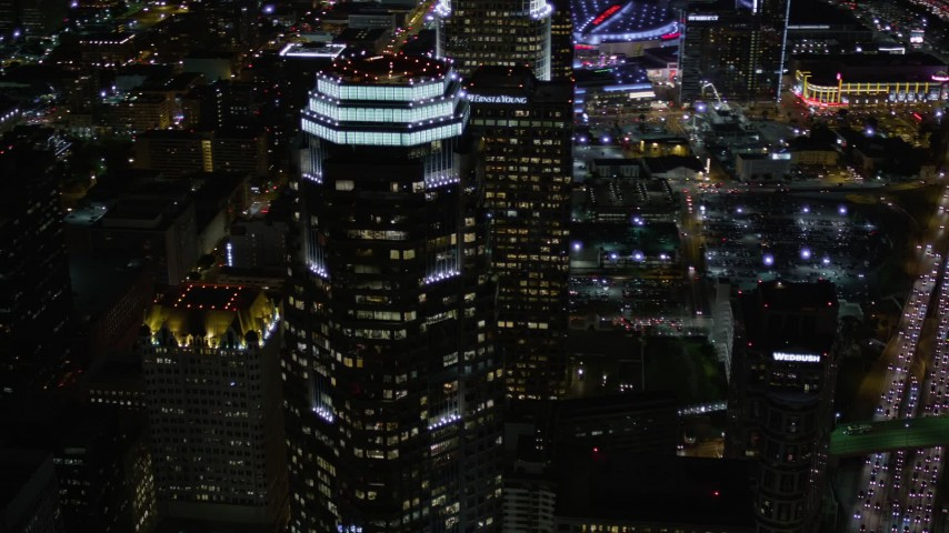 5K stock footage aerial video orbit and fly away from Figueroa at Wilshire at night in Downtown Los Angeles, California Aerial Stock Footage | AX0004_030