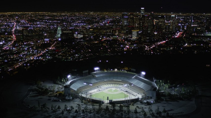 5K stock footage aerial video orbit Dodger Stadium and tilt to reveal Downtown Los Angeles at night, California Aerial Stock Footage | AX0004_034