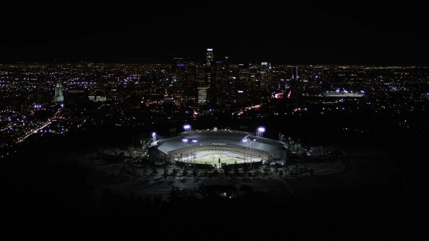 5K stock footage aerial video tilt to reveal Dodger Stadium and Downtown Los Angeles skyline at night, California Aerial Stock Footage | AX0004_036