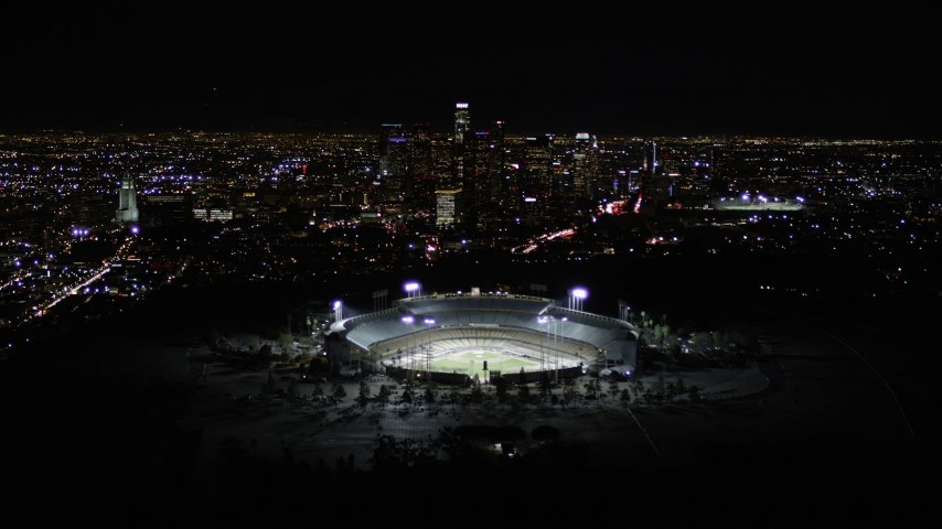 5K stock footage aerial video fly over Dodger Stadium to approach Downtown Los Angeles at night, California Aerial Stock Footage | AX0004_037