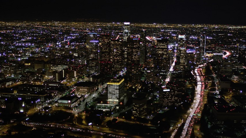 5K stock footage aerial video tilt up to reveal and approach Downtown Los Angeles at night, California Aerial Stock Footage | AX0004_038