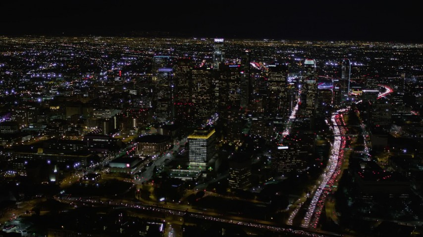 5K stock footage aerial video tilt up to reveal and approach Downtown Los Angeles at night, California Aerial Stock Footage | AX0004_038E