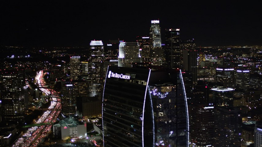 5K stock footage aerial video of Ritz-Carlton Hotel and Downtown Los Angeles skyscrapers at night, California Aerial Stock Footage | AX0004_045