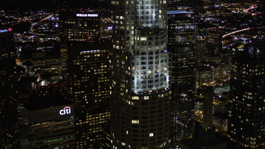 5K stock footage aerial video flyby US Bank Tower and approach Wells Fargo Center at night in Downtown Los Angeles, California Aerial Stock Footage | AX0004_060