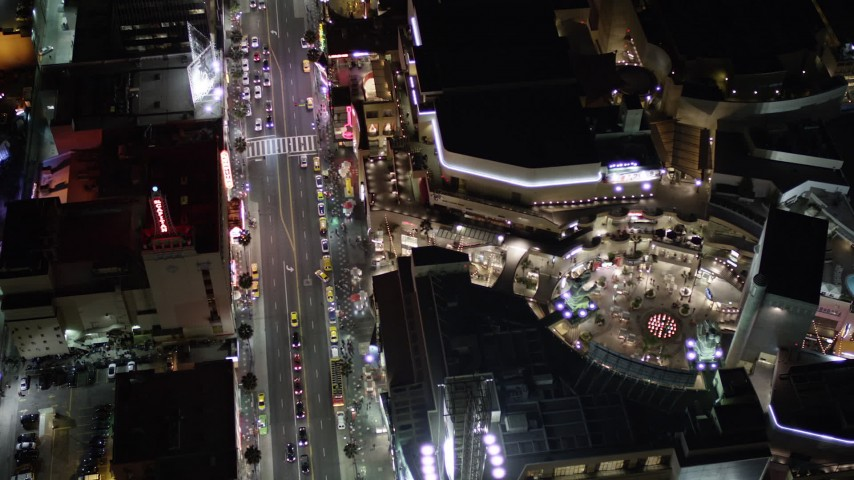 5K stock footage aerial video tilt to a bird's eye of Hollywood Boulevard and Hollywood and Highland Center at night, California Aerial Stock Footage | AX0004_077