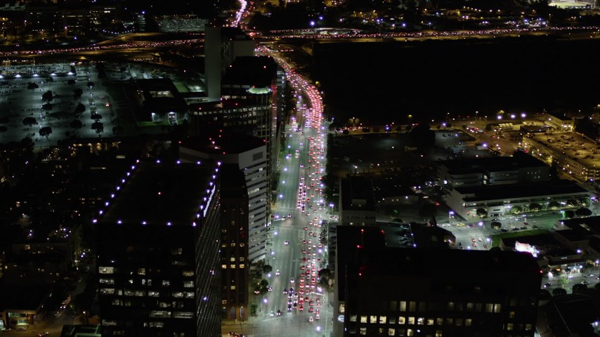 Fly Over and Tilt Down to Traffic on Wilshire Boulevard at Night  Aerial Stock Footage | AX0004_090