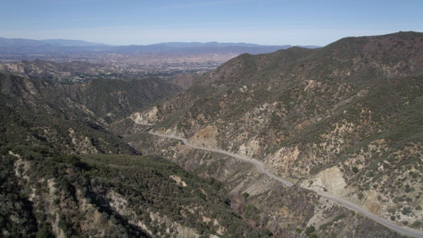 5K stock footage aerial video fly over a mountain to reveal a road through San Gabriel Mountains, California Aerial Stock Footage | AX0005_007